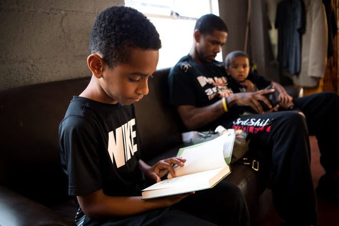 Demetrius Shelton, 9, of Nashville, reads a book from a mini-library at Moguls Barber and Lounge in Nashville, Tenn., Saturday, Aug. 25, 2018. As part of a new community initiative focused on literacy, several agencies are putting little libraries into everyday places where MNPS students congregate.