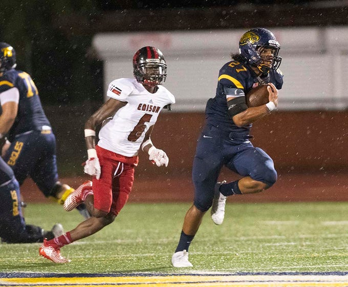 Chez Mellusi of Naples runs past Levan Jones of Miami-Edison for a touchdown during the game at Naples High Friday night, August 24, 2018.