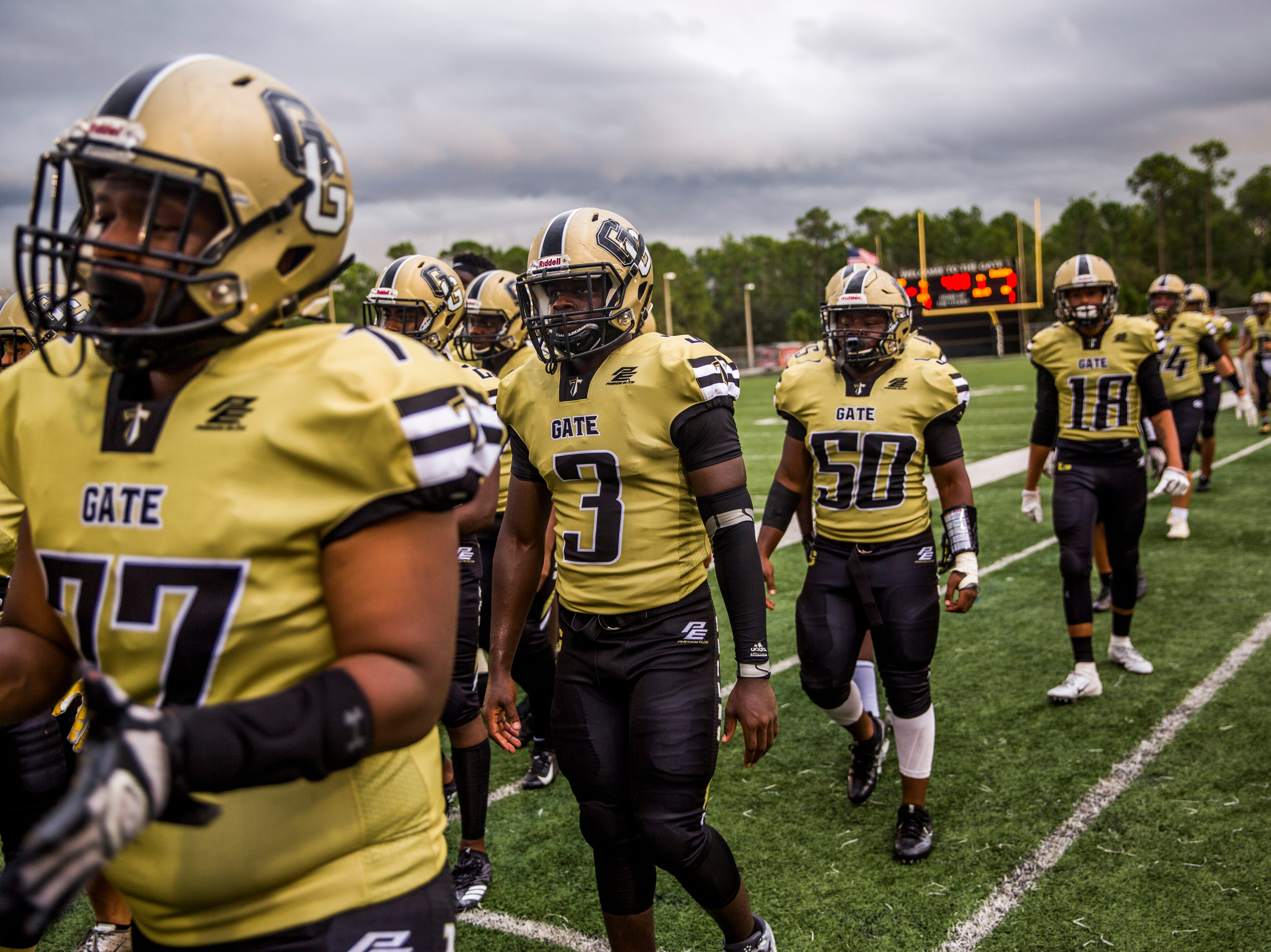 Golden Gate players leave the field during a lightning delay during the game against Immokalee at Golden Gate High School on Friday, Aug. 24, 2018.