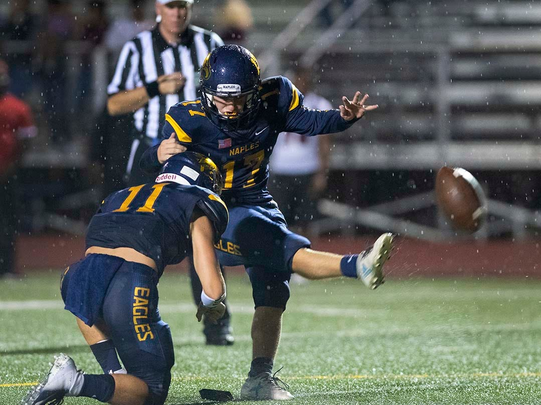 Nick Herber of Naples kicks an extra point from the hold by Mason Belyea during the game against Miami-Edison at Naples High Friday night, August 24, 2018.