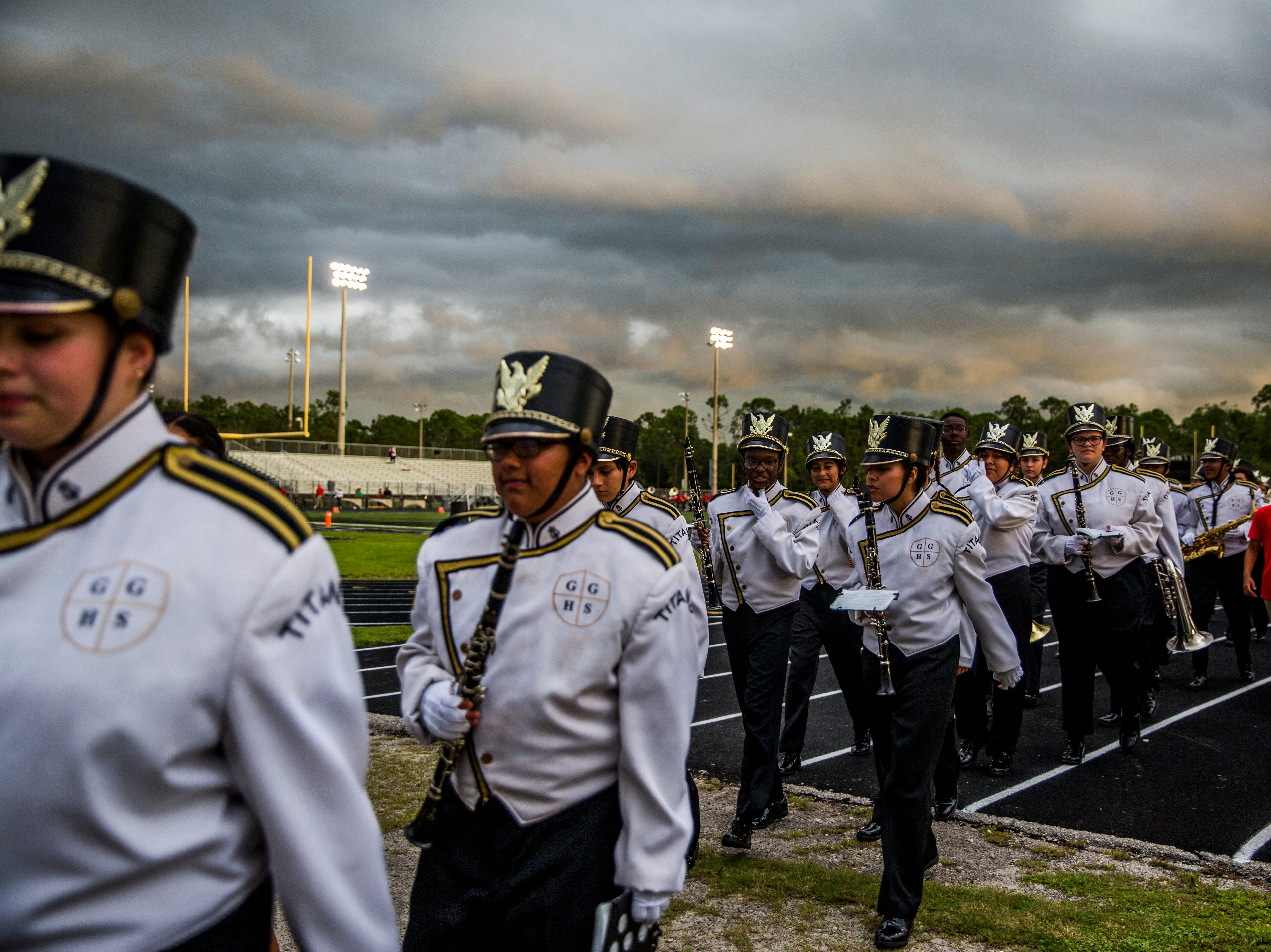 Golden Gate band members leave the field during a lightning delay during the game against Immokalee at Golden Gate High School on Friday, Aug. 24, 2018.