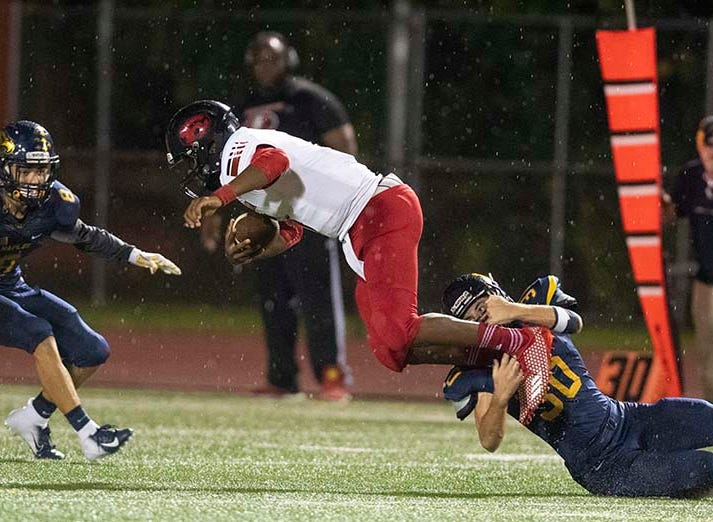 Jordan Magher of Naples brings down Miami-Edison quarterback Karon Johnson during the game at Naples High Friday night, August 24, 2018.
