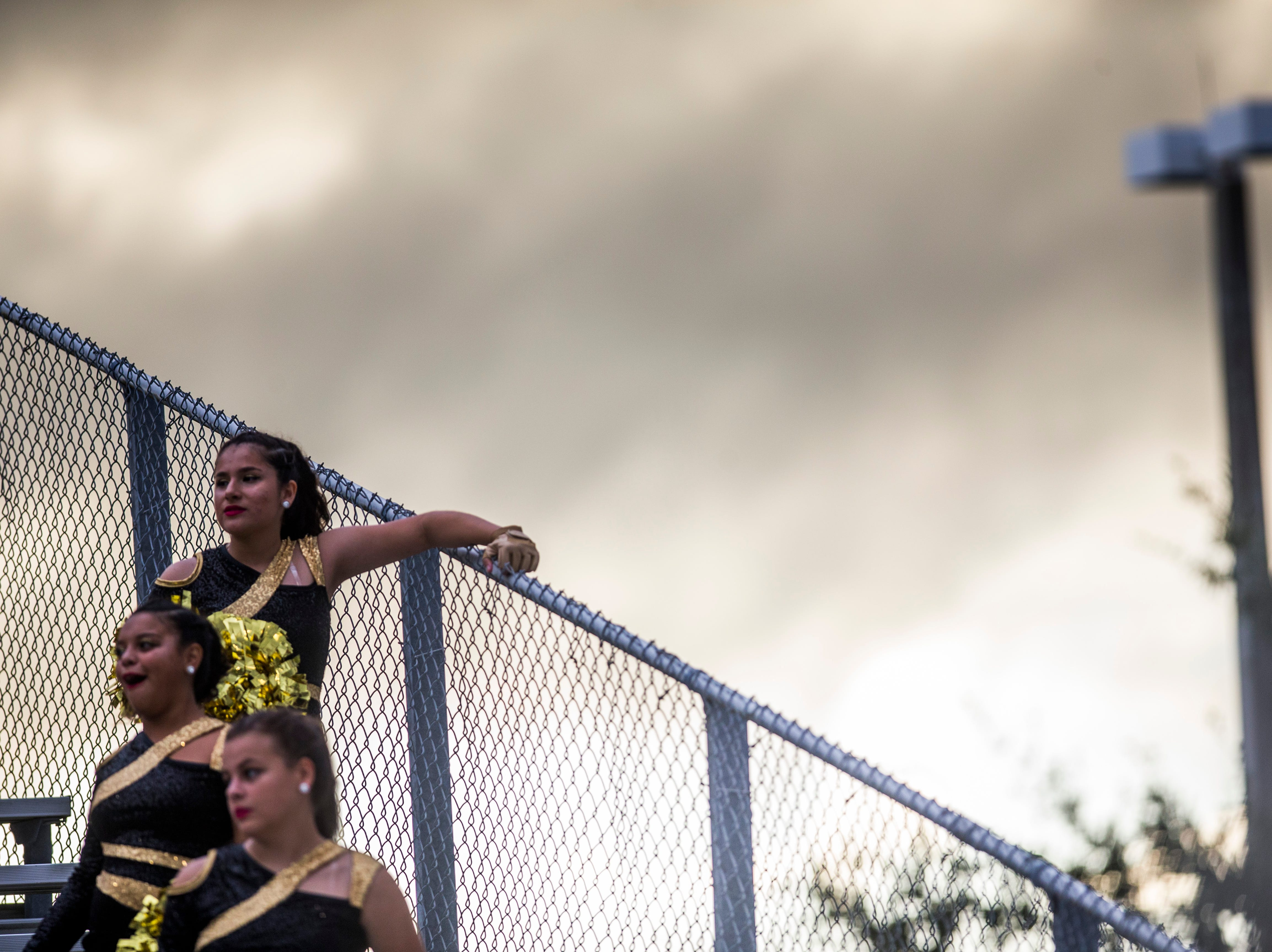 Golden Gate dancers watch from the bleachers during the game against Immokalee at Golden Gate High School on Friday, Aug. 24, 2018.