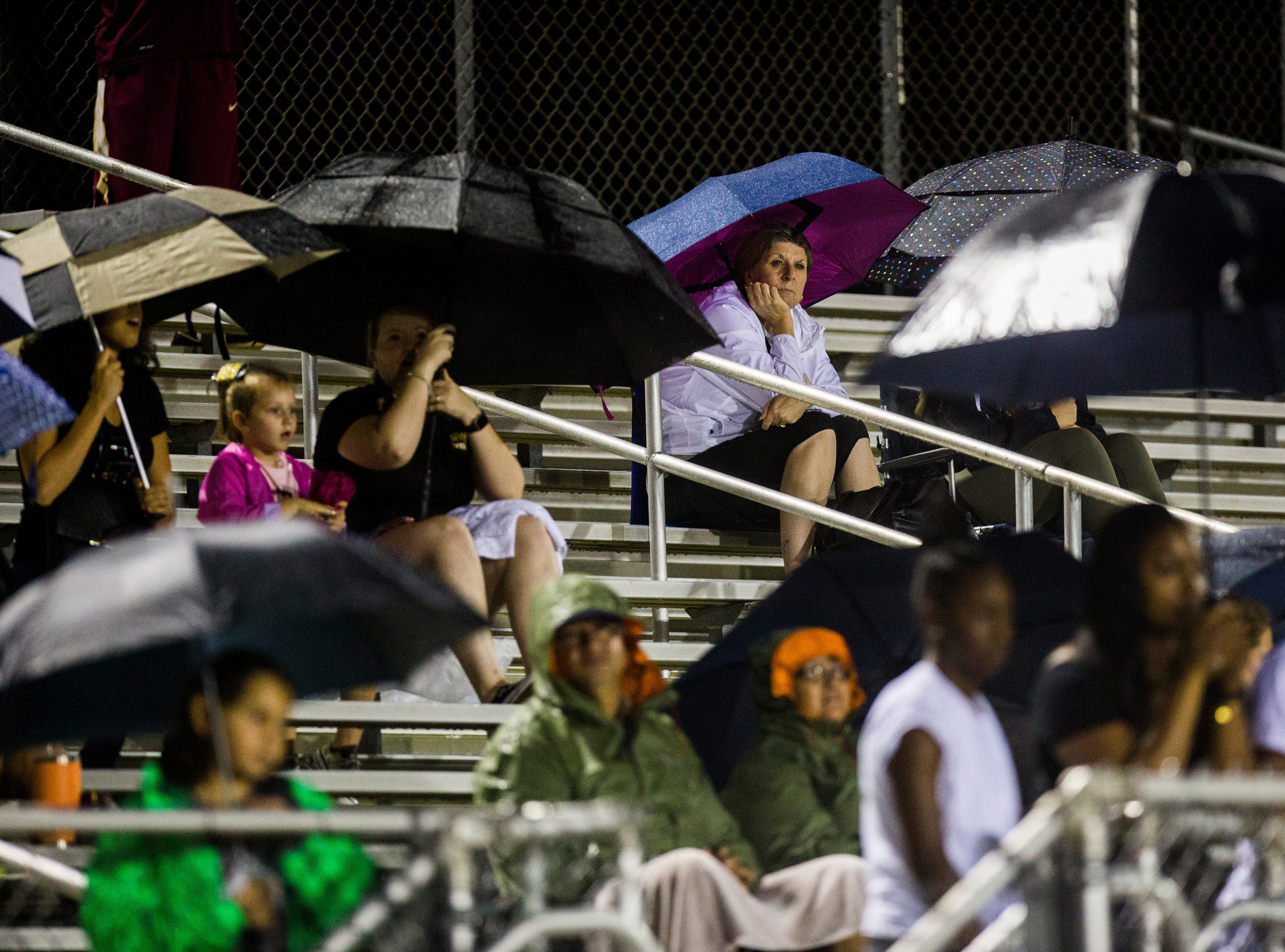 Spectators watch the game from the bleachers in the rain during the game against Immokalee at Golden Gate High School on Friday, Aug. 24, 2018.