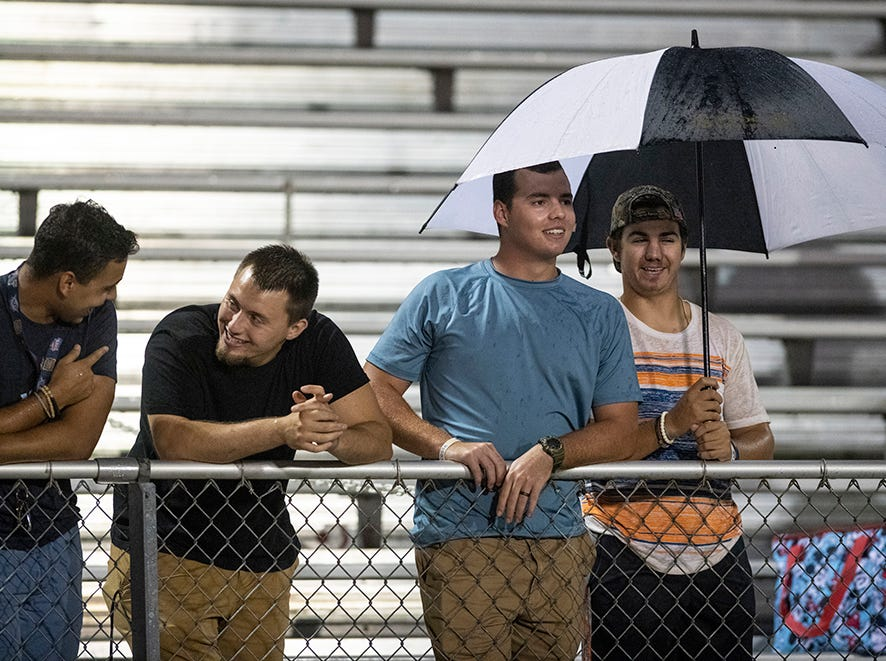 Fans watch the game in the rain at Naples High Friday night, August 24, 2018.