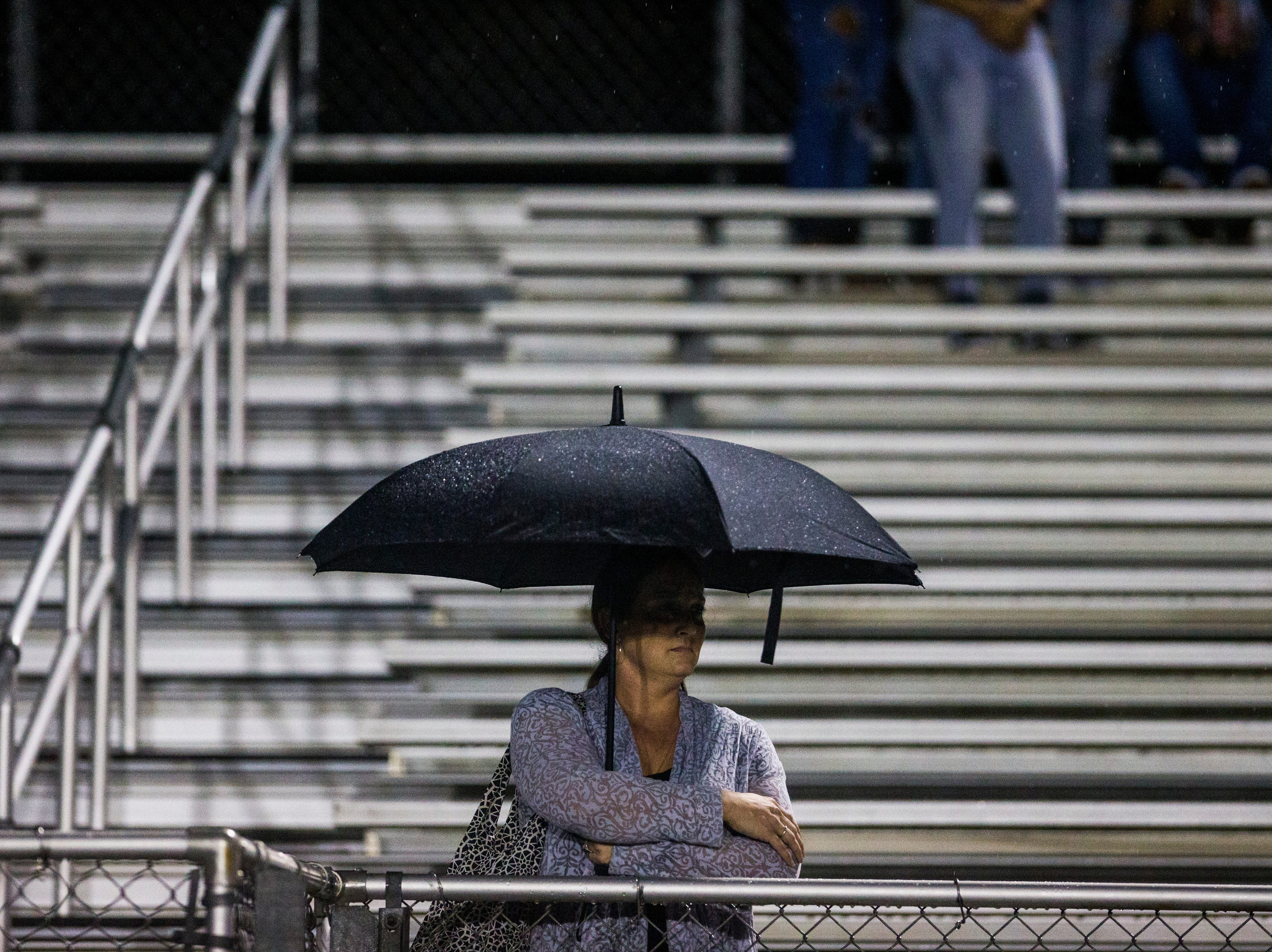 Spectators watch from the bleachers in the rain during the game against Immokalee at Golden Gate High School on Friday, Aug. 24, 2018.