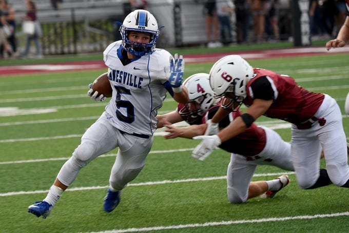 Zanesville senior J.C. Curts dodges Newark defenders senior Sam Loughman and junior Delrue Daniels uring Friday night's season-opener at White Field in Newark.The Blue Devils defeated the Wildcats 32-27.