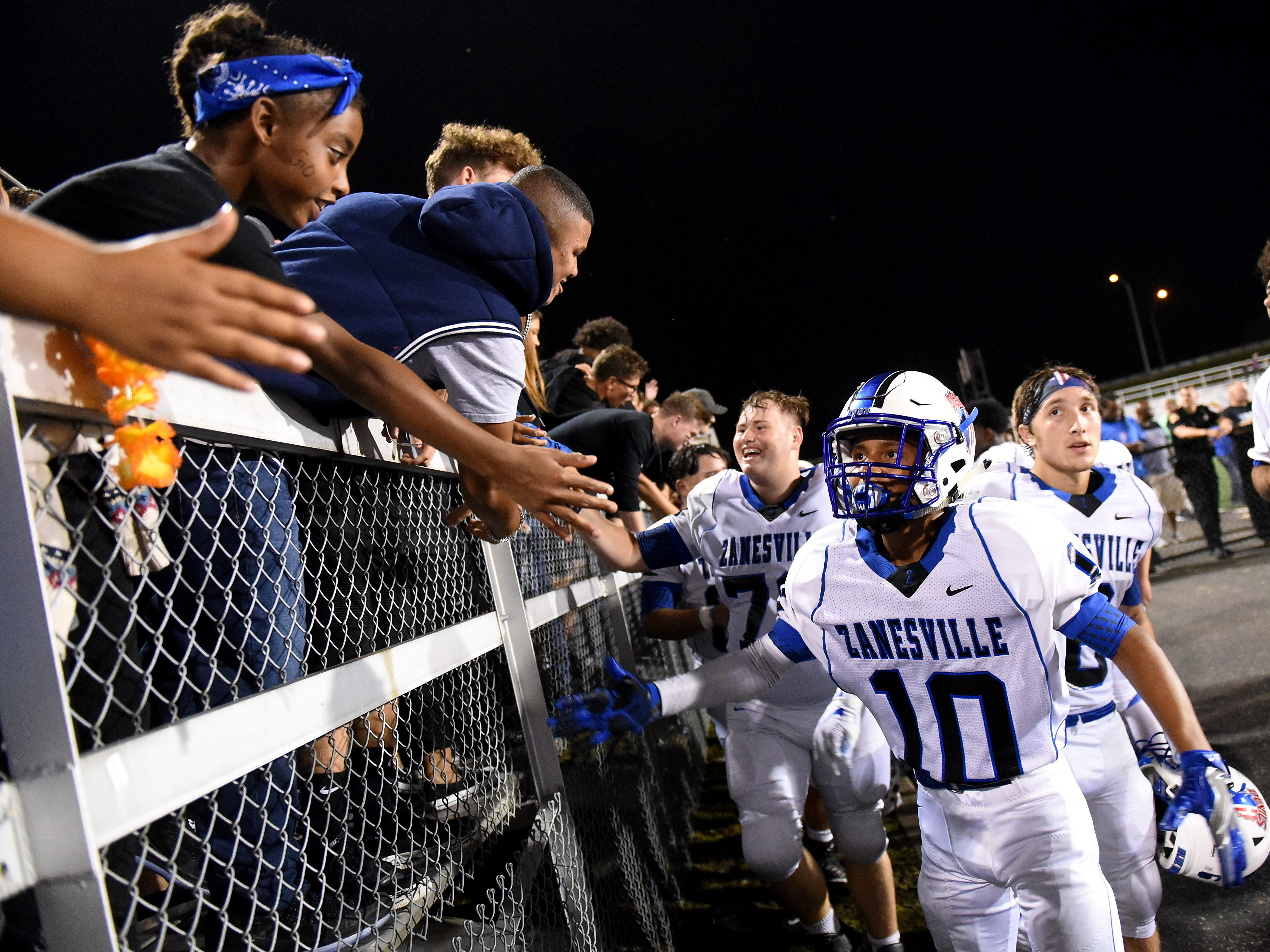Zanesville junior Jeremiah Norman (right) high fives members of the student section after the Blue Devils' 32-27 against Newark on Friday, Aug. 24, 2018.