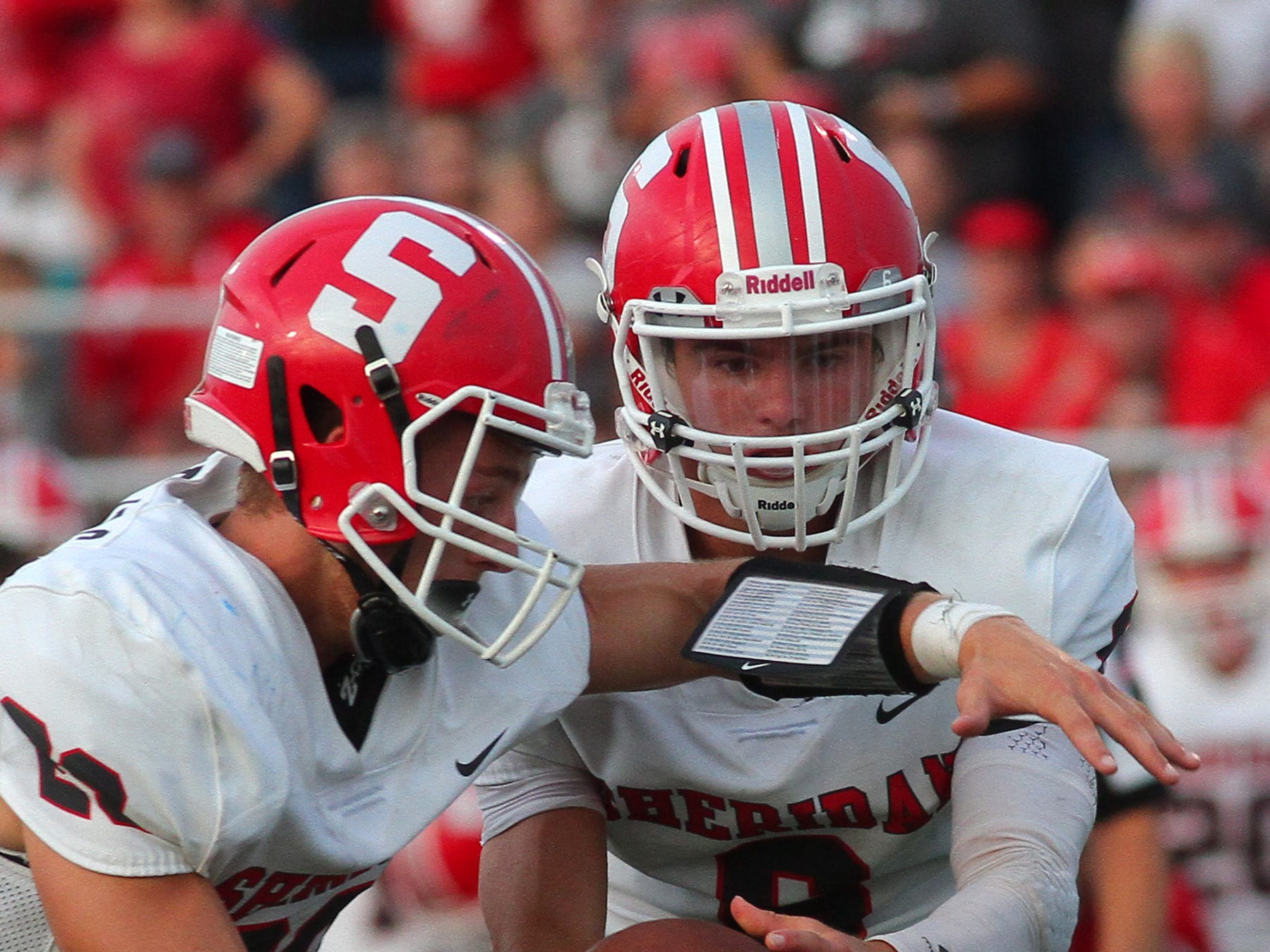 Sheridan senior quarterback Ethan Heller hands the ball to senior Jacob Morgan Friday during the team's 36-21 victory over Licking Valley.