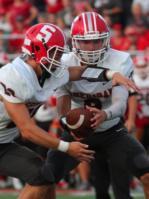 Sheridan senior quarterback Ethan Heller hands the ball to senior Jacob Morgan Friday during the team's 36-21 victory over Licking Valley. Heller passed for a school-record 304 yards.