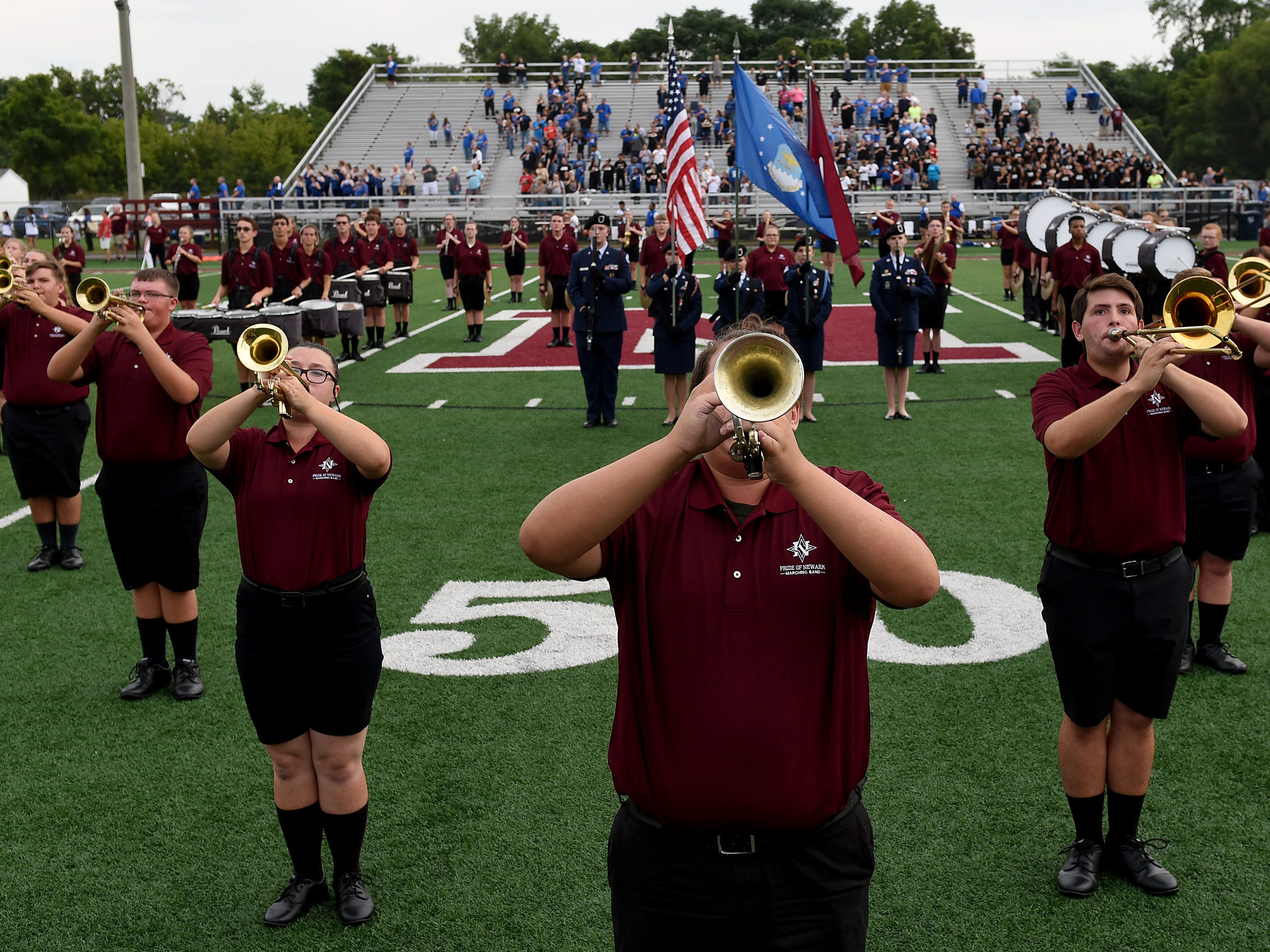 The Newark High School marching band performs the national anthem as Air Force Junior ROTC presents the colors before the start of the first football game of the 2018 season on Friday, Aug. 24, 2018 at White Field.