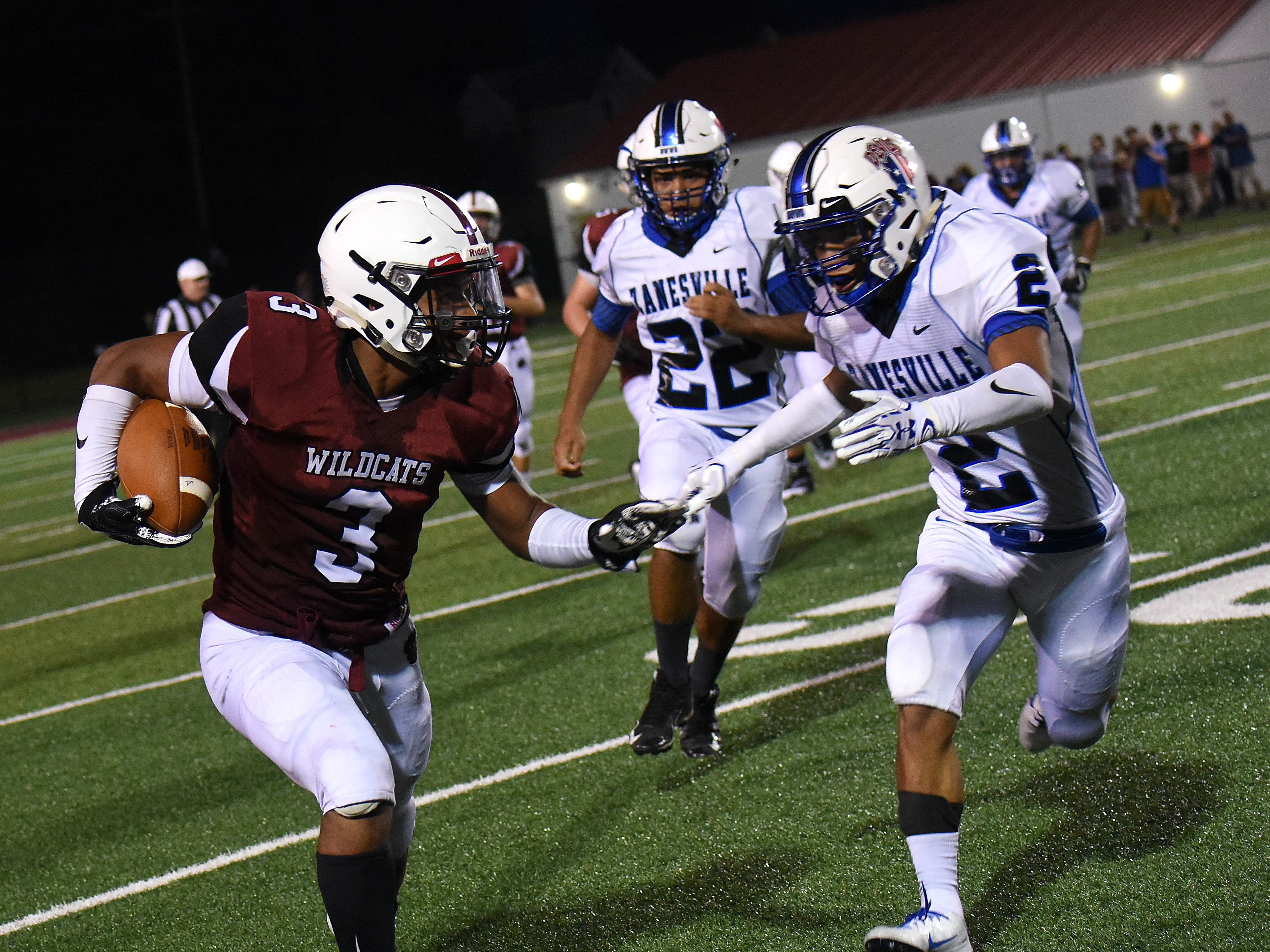 Newark senior running back Davian Williams tries to dodge Zanesville defender junior Zarek Morgan during Friday night's season opening game at White Field in Newark. The Blue Devils defeated the Wildcats 32-27.