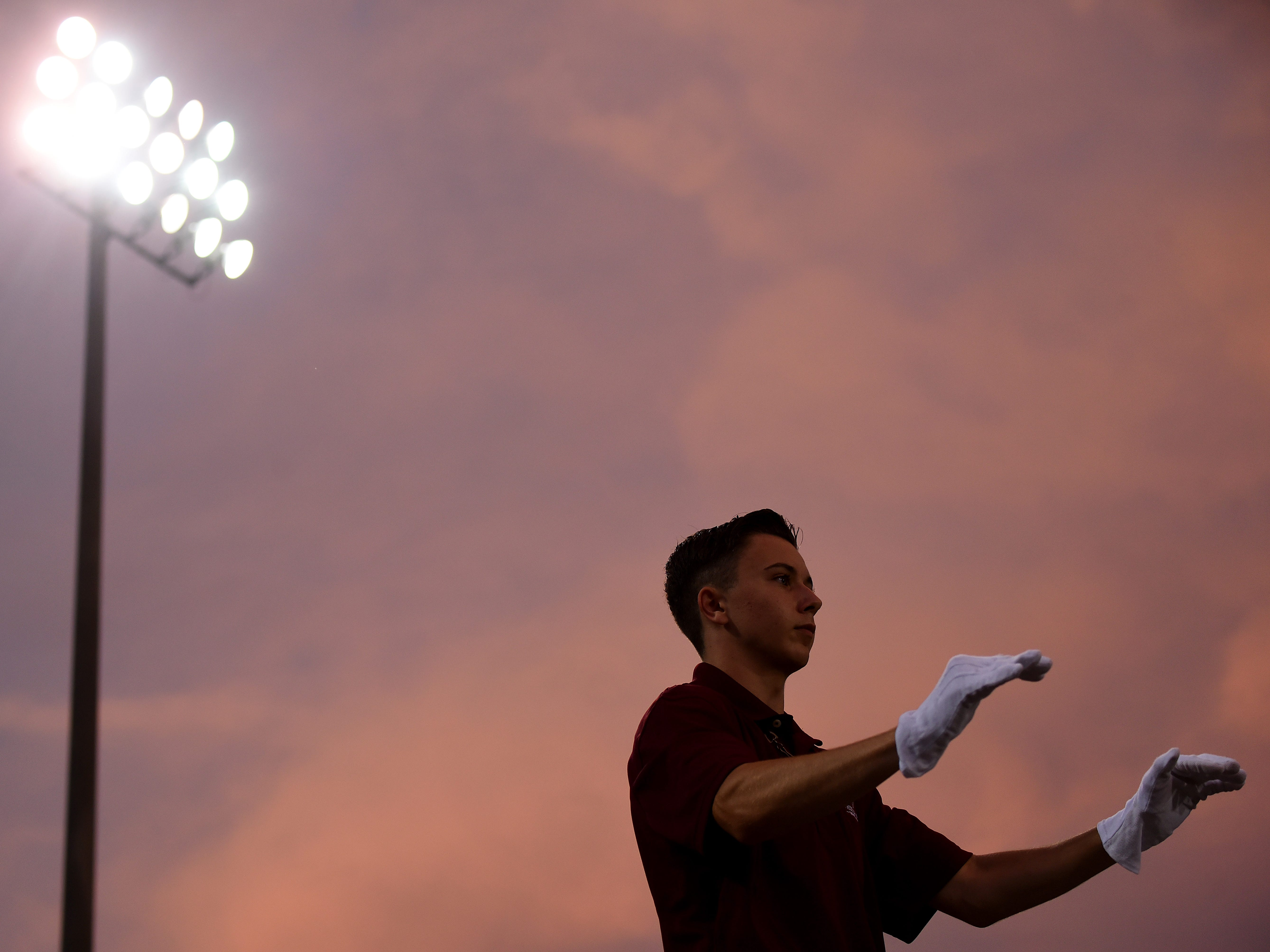 Newark High School Marching Band drum major Tyler Cornwell leads the band during halftime on Friday, Aug. 24, 2018.