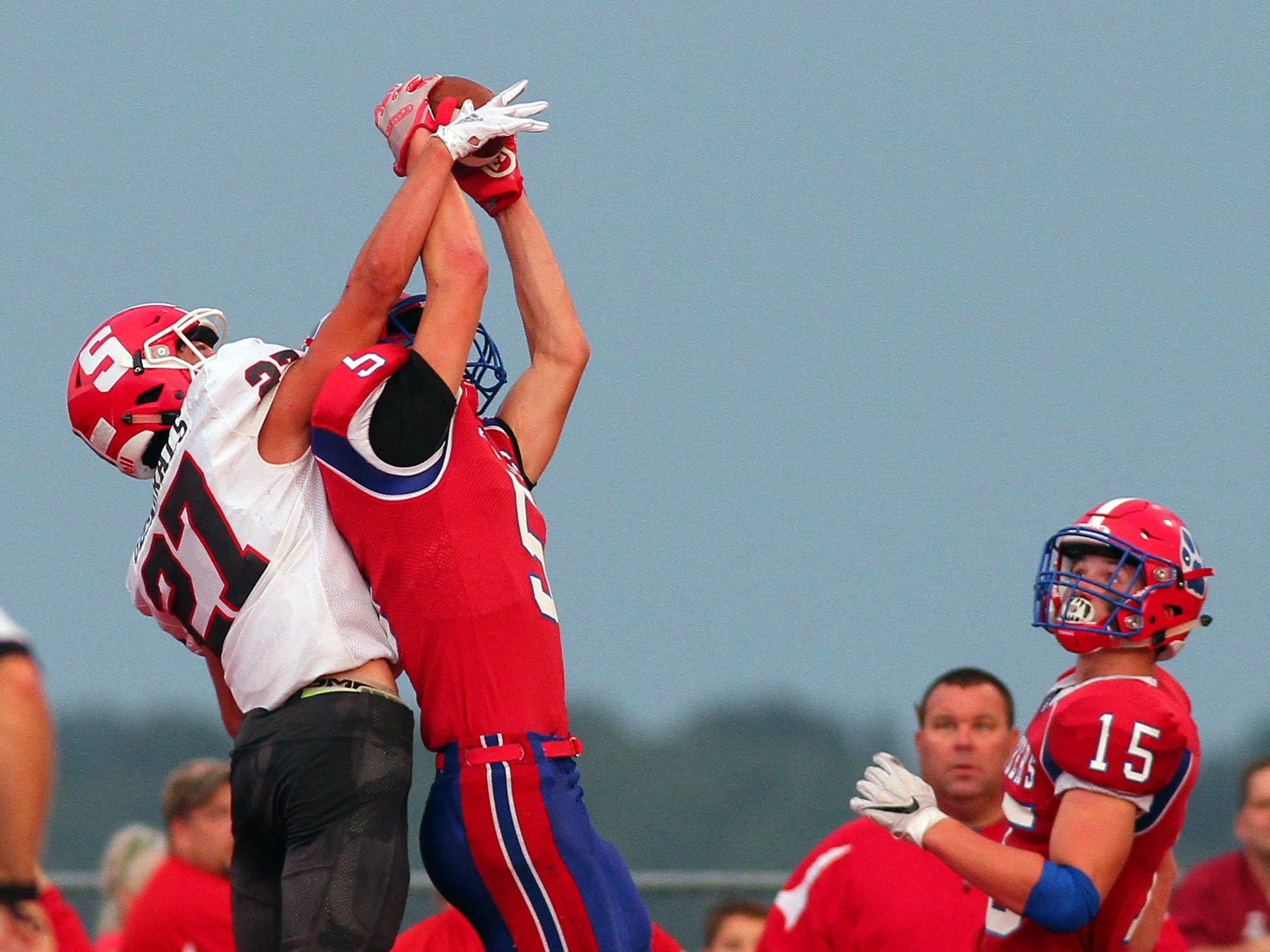 Licking Valley junior Carson Conley completes a touchdown pass under pressure from Sheridan senior Jacob Rhodes Friday during the Panthers' 36-21 loss to the Generals.