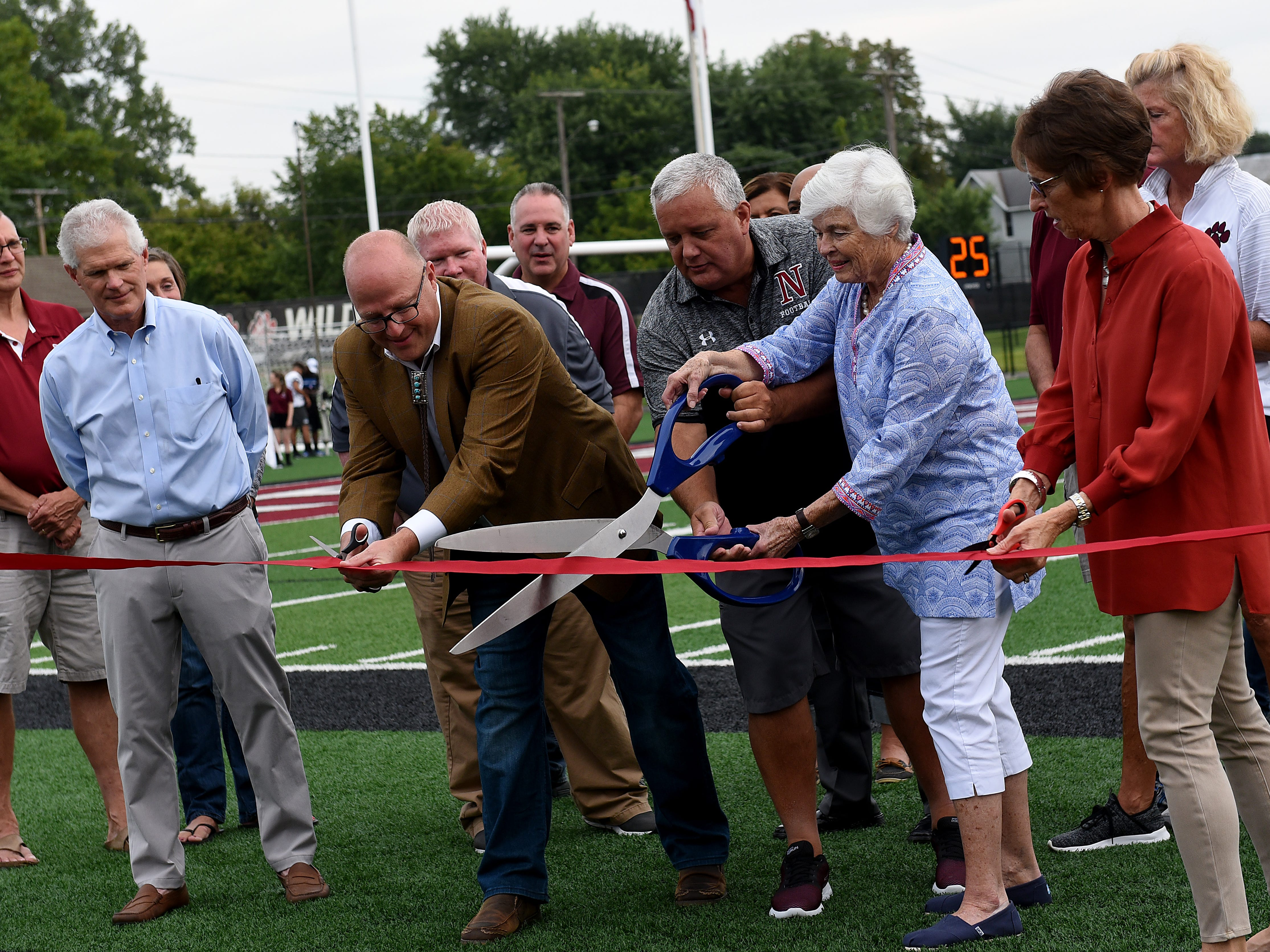 "Bronze sculptor Scott Rogers, Newark superintendent Doug Ute, Lou Reese, and Sarah Wallace cut the ribbon for the new statue at White Field, ""Football, Circe 1890"". The statue was installed thanks to a donation from the Gilbert Reese Family Foundation."