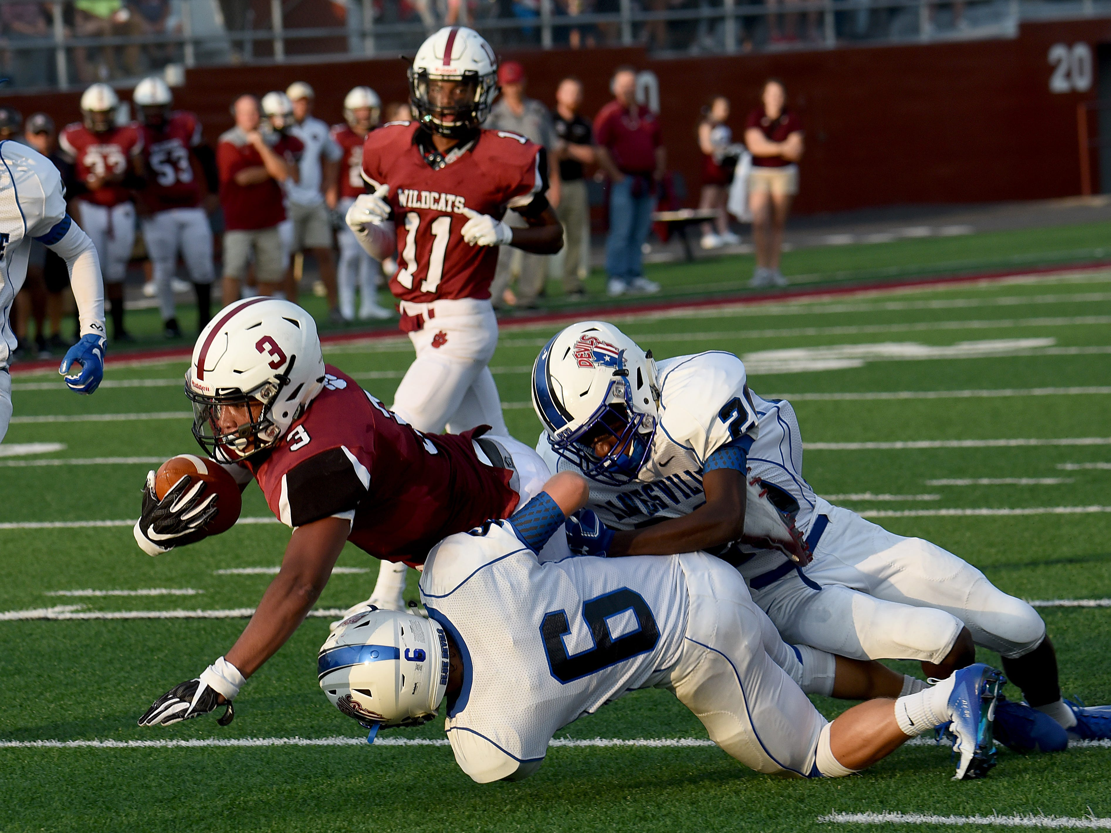Newark senior running back Davian Williams reaches for yardage as he is brought down by Zanesville defenders senior Slade Norris and junior Jamal Wiggins during Friday night's season opening game at White Field in Newark. The Blue Devils defeated the Wildcats 32-27.