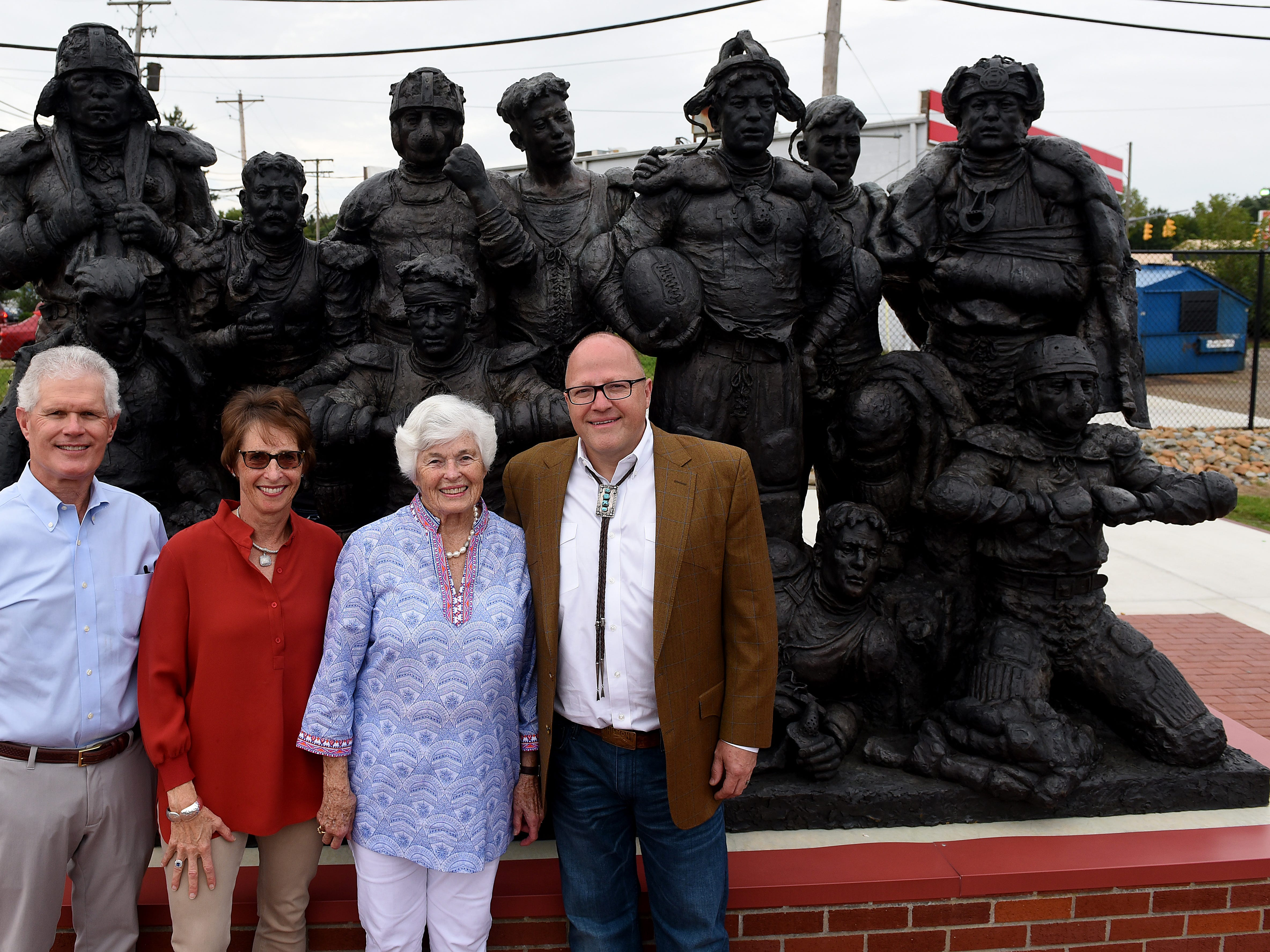 "John Wallace, Sarah Wallace, Lou Reees and artist Scott Rogers pose with the newly installed ""Football, Circa 1890"" statue at White Field. The statue, by the Utah based artist, is a a donation from the Gilbert Reese Family Foundation."