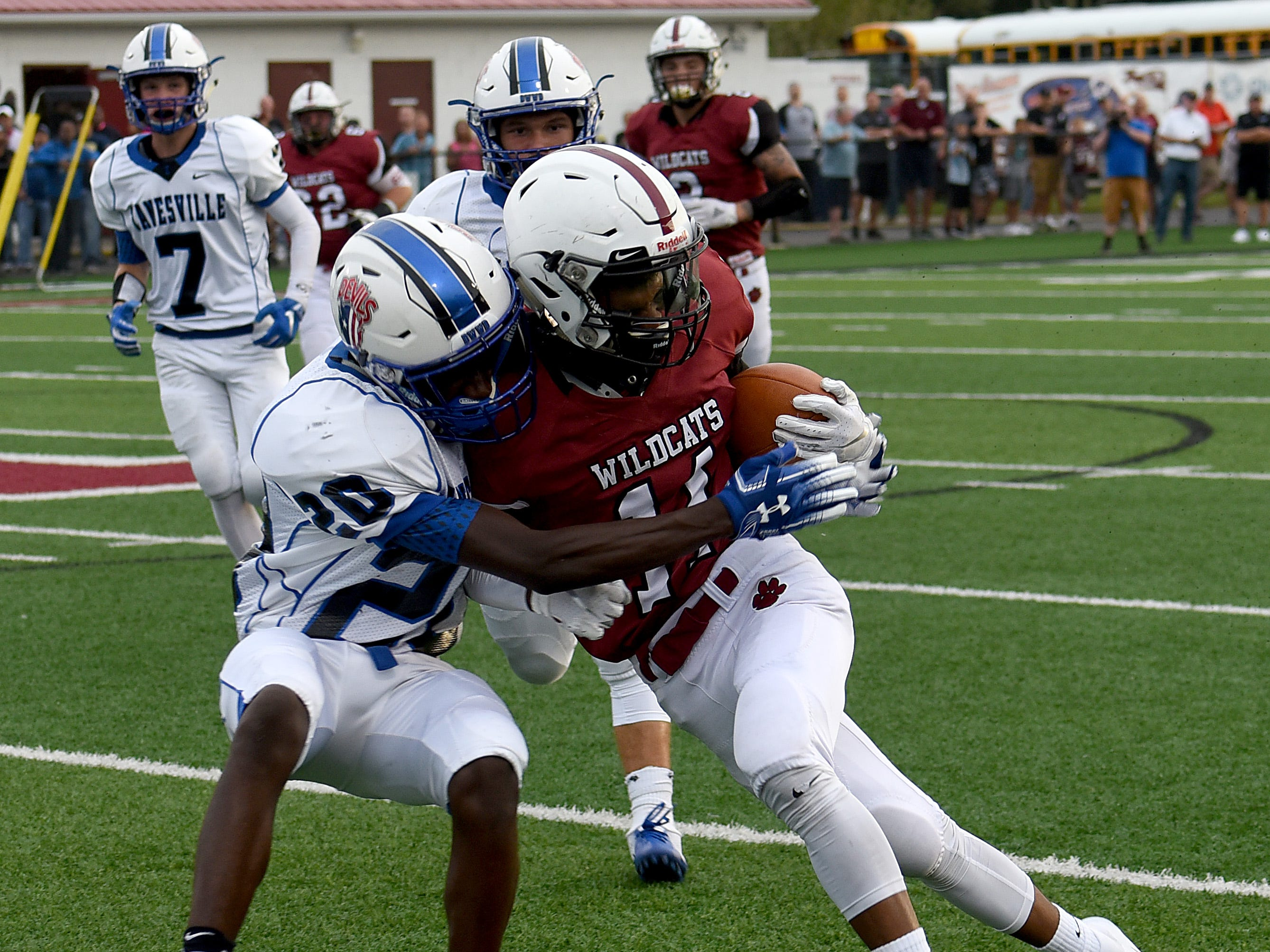 Zanesville junior Jamal Wiggins tackles Newark wide receiver Dustin Williams during Friday night's season opening game at White Field in Newark. The Blue Devils defeated the Wildcats 32-27.
