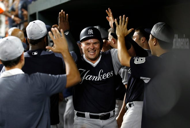 New York Yankees' Luke Voit, center, high-fives teammates in the dugout after hitting a two-run home run in the 10th inning of a baseball game against the Baltimore Orioles, Friday, Aug. 24, 2018, in Baltimore.