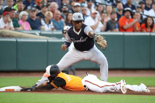 Baltimore Orioles outfielder Cedric Mullins (3) slides safely into third base after advancing on a fly ball out against the New York Yankees at Oriole Park at Camden Yards.