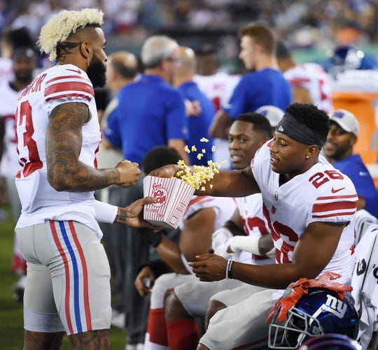 Giants vs. Jets preseason game at MetLife Stadium in East Rutherford on Friday, August 24, 2018. G #13 Odell Beckham Jr. and #26 Saquon Barkley eat popcorn in the fourth quarter.