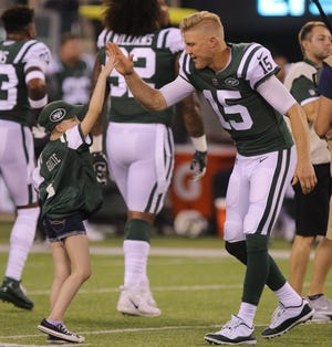 The Jets honorary captain for tonight's game, Grace Eline of Gillette, NJ and Jets quarterback Josh McCown as Grace leaves the field after the coin toss.