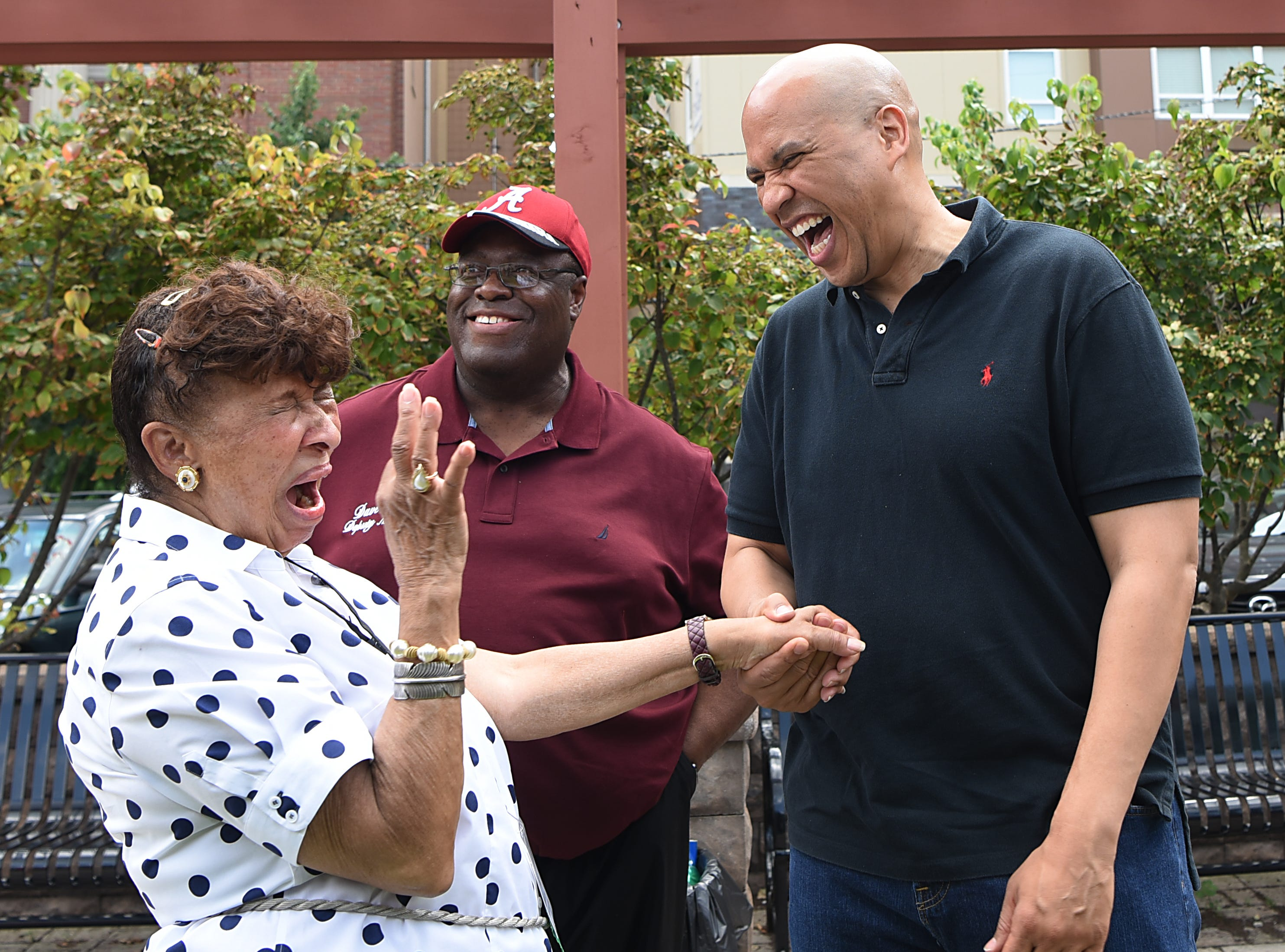 Lee Porter and Senator Cory Booker share a laugh along with Dave Sims. Fair Housing Council of Northern New Jersey holds a picnic in Hackensack on Friday August 10, 2018.