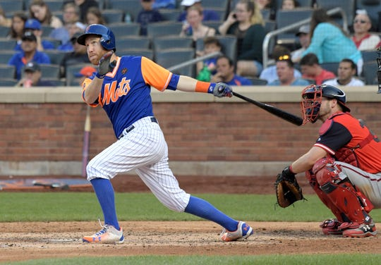 New York Mets' Todd Frazier follows through on a home run as Washington Nationals catcher Matt Wieters, right, looks on during the seventh inning of a baseball game Saturday, Aug. 25, 2018, in New York.