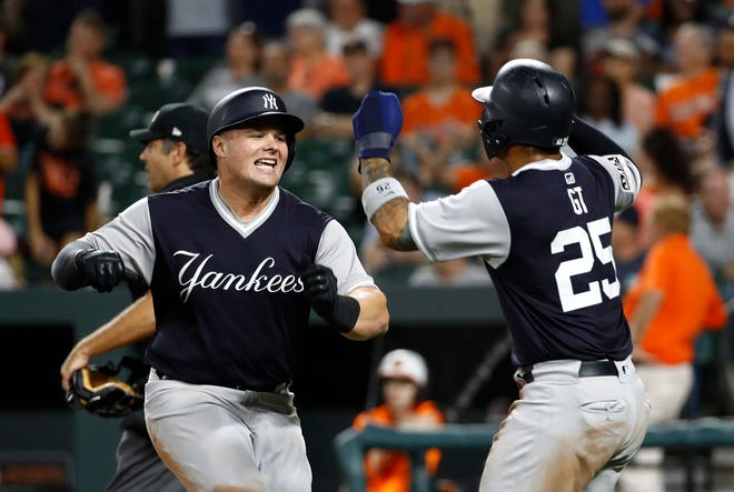 New York Yankees' Luke Voit, left, celebrates with teammate Gleyber Torres after batting him in on a two-run home run in the 10th inning of a baseball game against the Baltimore Orioles, Friday, Aug. 24, 2018, in Baltimore.