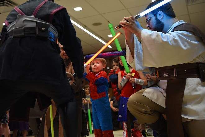 (Center) Ricardo Romero, three years old, learns how to wield a light saber with guidance from John Hoffman (right) dressed as Master Agamar, during the Saber Guild class. Comic-Con at Bergenfield Public Library in Bergenfield on Saturday August 25, 2018.