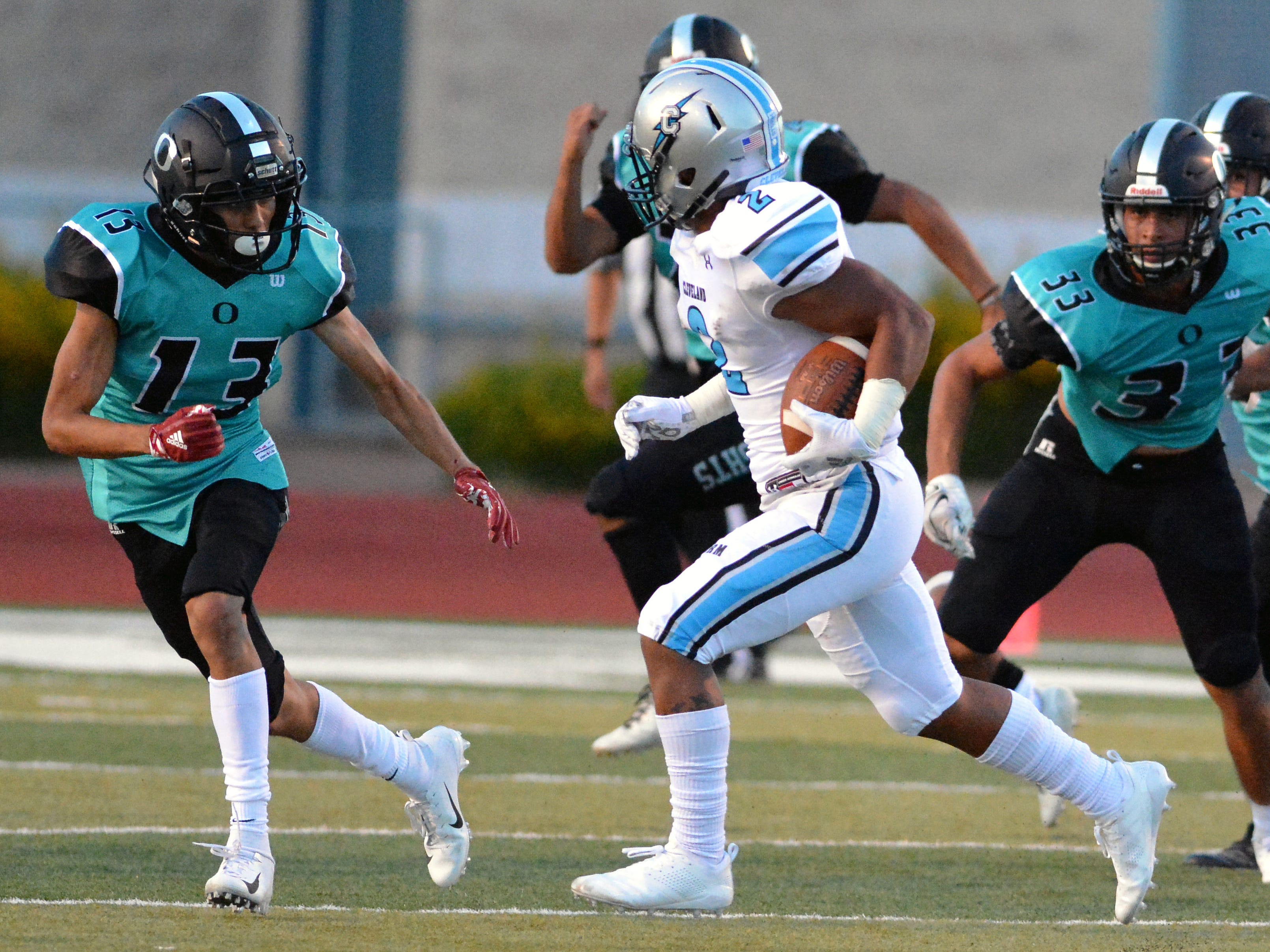 Oñate defensive back Justin Gutierrez (13) and Linebacker Daniel Diaz (33) get ready to tackle Cleveland's Dorian Lewis Friday night at the Field of Dreams.