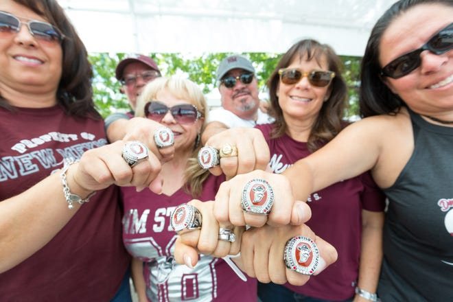 New Mexico State University Alumni wear their replica Nova Home Loans Arizona Bowl rings during tailgating on Saturday, August 25, 2018, in the parking lots of Aggie Memorial Stadium. Those who renewed their season ticket this year received the ring complementary. Pictured from left, Elena Glaze, Elaine Armijo, Gerry Brown-Encinias, Eloy Armijo, Maria Rodriguez and Angela Armijo.