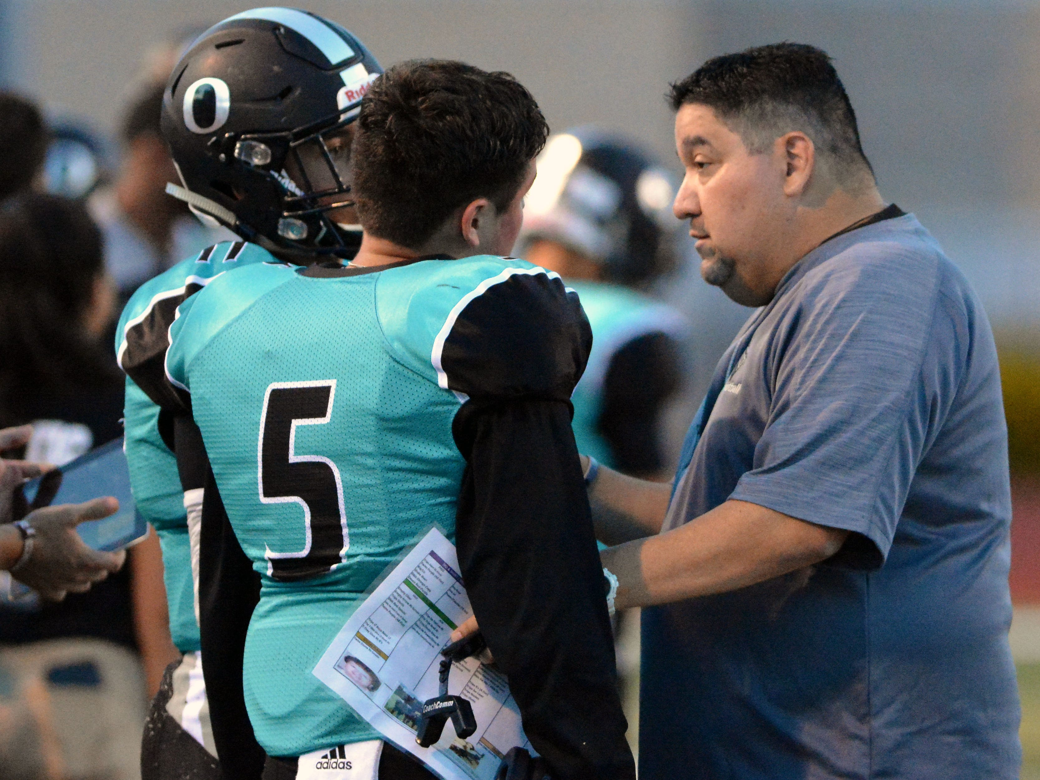 Oñate head coach Scott Veliz, right, talks to Jayden Diaz, left, and Brandon Veliz (5) during a timeout against Cleveland Friday night at the Field of Dreams.