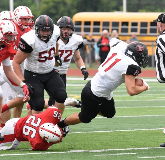 Churchill quarterback Drew Alsobrooks (11) fights for extra yardage as he tries to elude Canton's Victor Mancuso in the season opener.