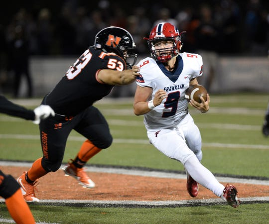 Franklin quarterback Jacob Kelbert (right) tries to elude Northville tackler Emile Rizk.