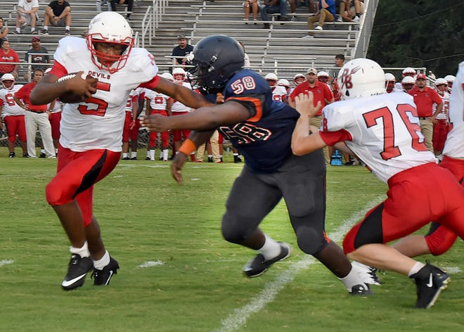 Port Barre quarterback Kyeron Malveaux attempts to escape the clutches of a Beau Chene defensive lineman as Dawson Desotell attempts a block. Port Barre defeated Beau Chene 7-0 in the St. Landry Parish Football Jamboree held Friday night at Donald Gardner Stadium.