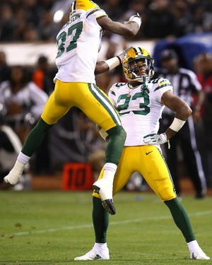 Green Bay Packers cornerback Jaire Alexander (23) celebrates with cornerback Josh Jackson (37) after Alexander intercepted an Oakland Raiders pass during the first half of an NFL preseason football game in Oakland, Calif., Friday, Aug. 24, 2018.