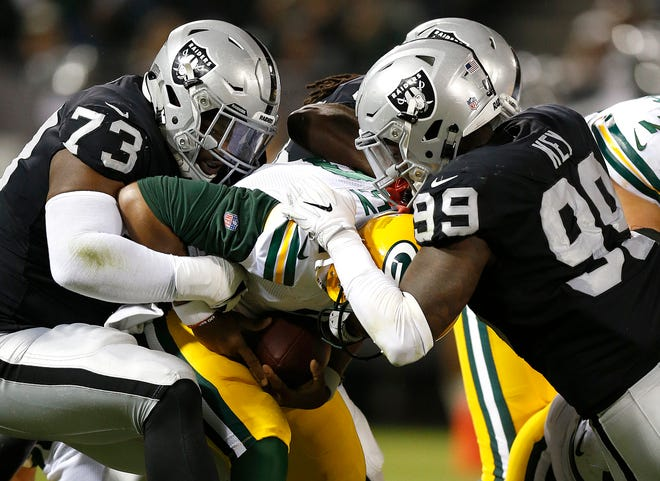 Green Bay Packers quarterback Brett Hundley, center, is sacked by Oakland Raiders defensive tackle Maurice Hurst (73) and defensive end Fadol Brown, obscured, during the first half of an NFL preseason football game in Oakland, Calif., Friday, Aug. 24, 2018. At right is Raiders defensive end Arden Key (99).