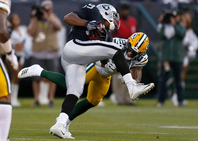 Oakland Raiders wide receiver Amari Cooper, top, runs against Green Bay Packers cornerback Jaire Alexander during the first half of an NFL preseason football game in Oakland, Calif., Friday, Aug. 24, 2018.