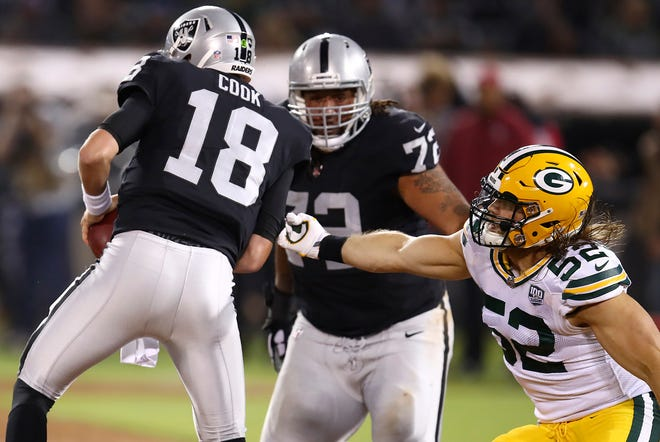 Green Bay Packers linebacker Clay Matthews (52) applies pressure to Oakland Raiders quarterback Connor Cook (18) during the first half of an NFL preseason football game in Oakland, Calif., Friday, Aug. 24, 2018.