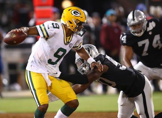 Oakland Raiders linebacker Nicholas Morrow, bottom, grabs Green Bay Packers quarterback DeShone Kizer (9) before sacking him during the second half of an NFL preseason football game in Oakland, Calif., Friday, Aug. 24, 2018.