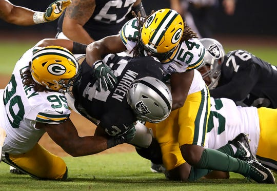 Oakland Raiders running back Chris Warren III, center, is tackled by Green Bay Packers defensive end James Looney (99) and linebacker James Crawford (54) during the second half of an NFL preseason football game in Oakland, Calif., Friday, Aug. 24, 2018.