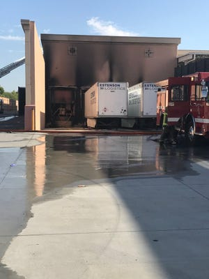 Scorch marks and smoke cover the outside of the rear loading dock area at Indio's Home Depot Friday after two semi-trucks caught fire in the load dock.