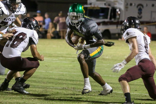 Pensacola Catholic's Demarius McGhee (6) pushes through the Navarre defenders for extra yards at Catholic High School on Friday, August 24, 2018.