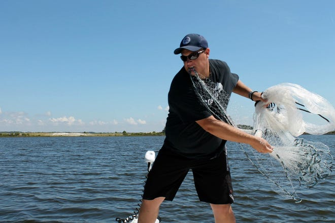 Captain Jeremy Hogue with Buck Wild Inshore Charters throwing his net on a school of mullet in Pensacola Bay.