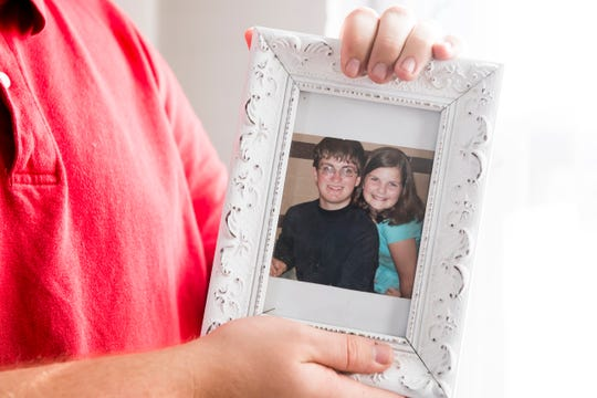 Woodrow Wagaman Jr. holds up a framed photo of himself and his sister, Rebekah, taken around the time he would have met Joseph Thornton, in 2010.
