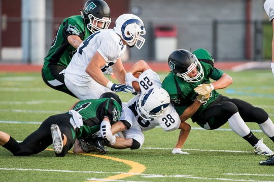 Fairfield's Joey Quealy, left, and Garrett Stadler, right, tackle Penns Valley's Ryan Ripka on August 24, 2018. The Knights fell 49-6.