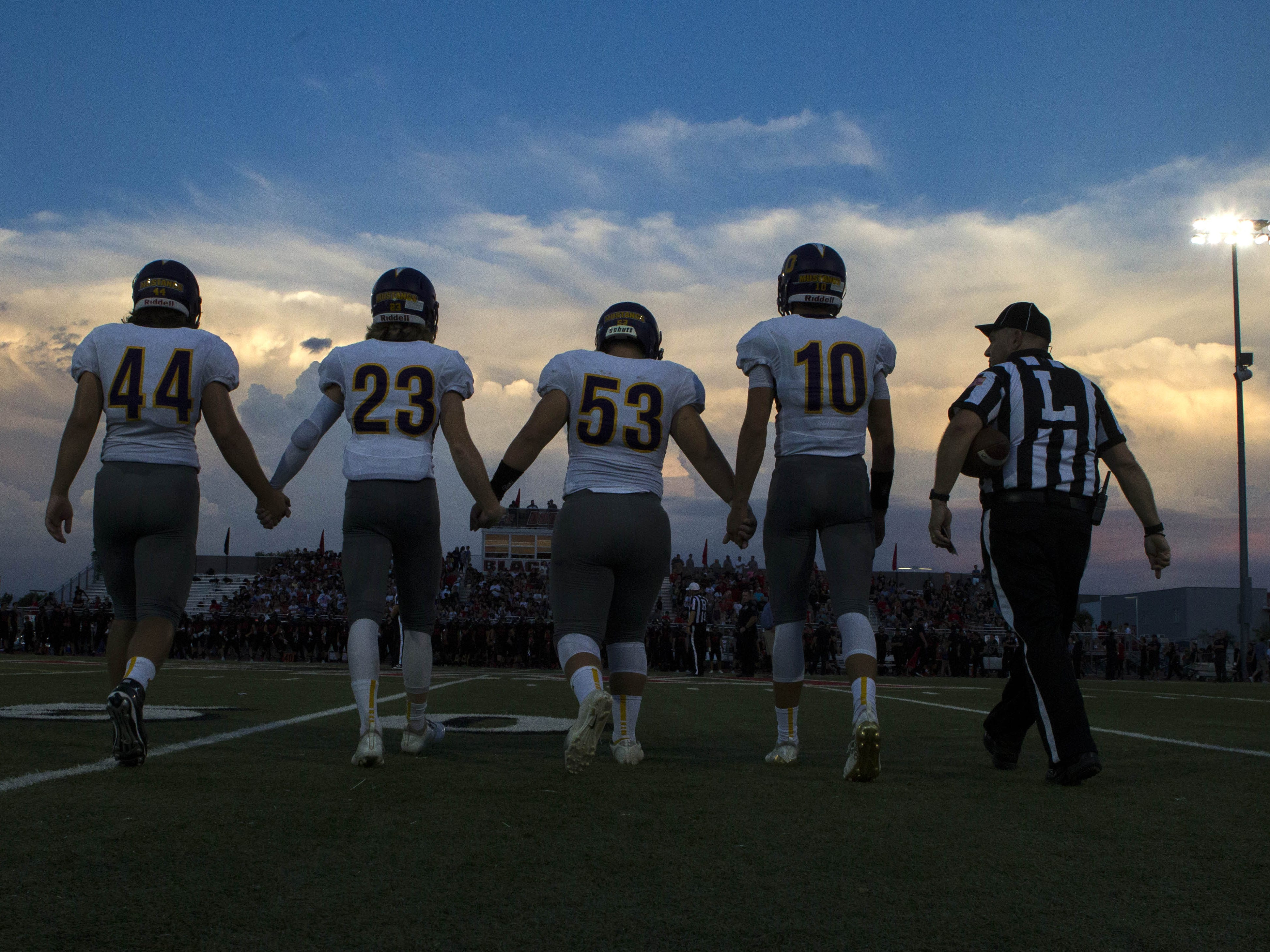 Sunrise Mountain captains walk to the center of the field for the coin toss before their game with Williams Field High School in Gilbert Friday, Aug.24, 2018.#azhsfb (Darryl Webb/For the Republic)