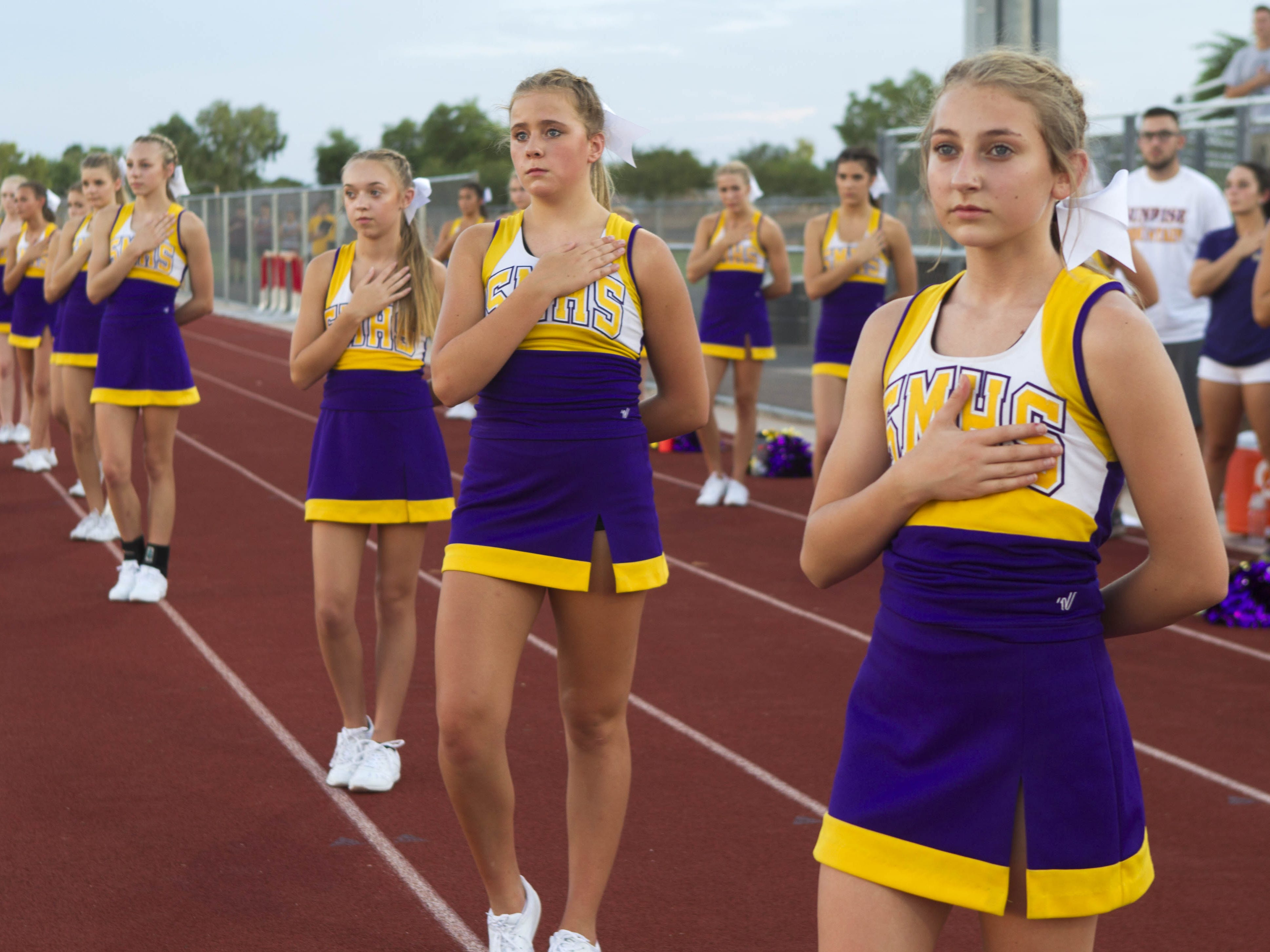 Sunrise Mountain cheerleaders salute the flag during the National Anthem before their game with Williams Field High School in Gilbert Friday, Aug.24, 2018.#azhsfb (Darryl Webb/For the Republic)