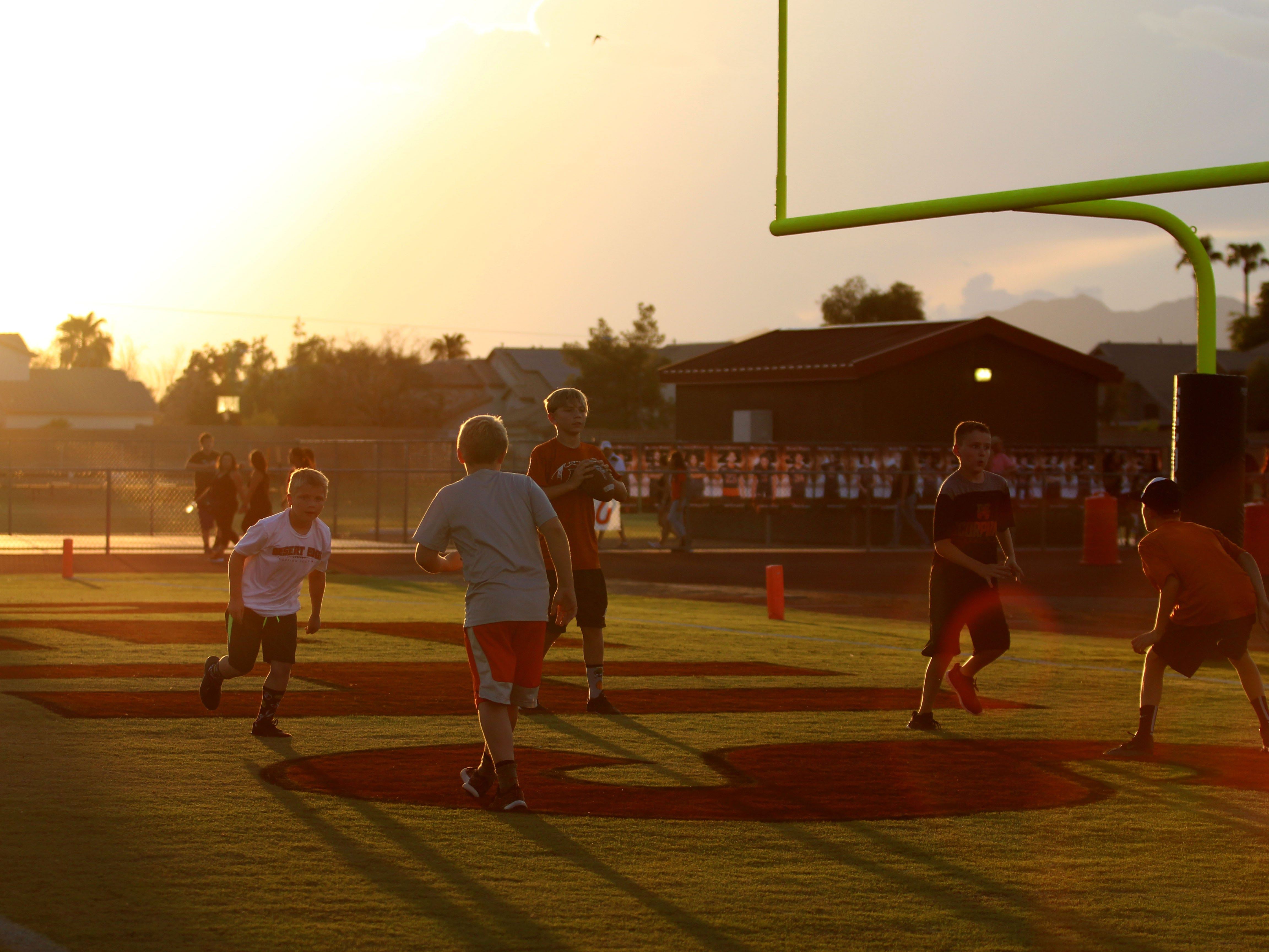 Kids play football on the field before Desert Edge plays Moon Valley, Goodyear, Ariz. August 24, 2018.